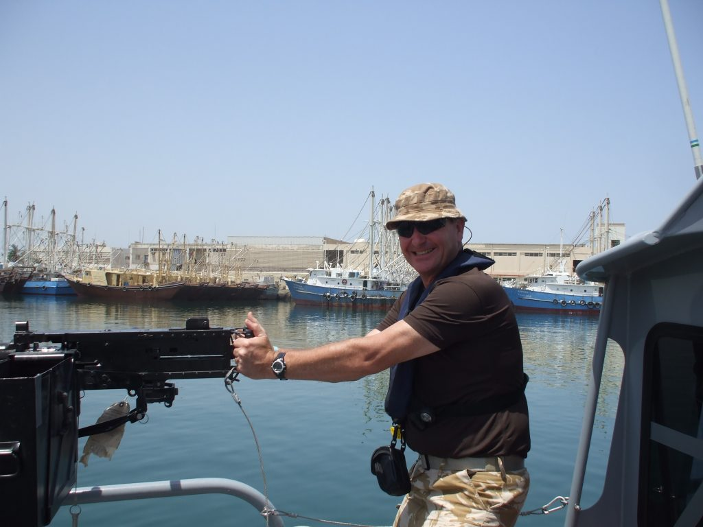 Uk soldier on US patrol boat in Kuwait